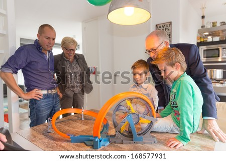 HELMOND, NETHERLANDS - OCTOBER 5, 2013: Children playing with a race track while the father and grandparents are watching.  - stock photo