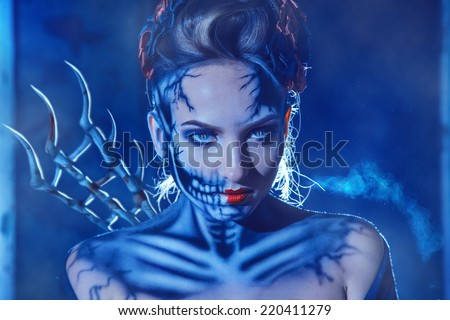 Heloween theme photo of sexy woman with face art of skull on face outdoors - stock photo