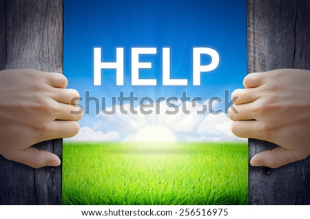 HELP. Hand opening an old wooden door and found HELP word floating over green field and bright blue Sky Sunrise. - stock photo