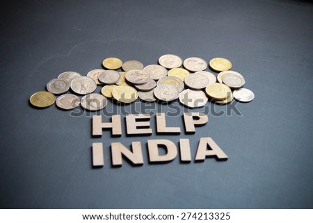 Help India with money is the concept here on blackboard. Wooden letters are here with different countries currencies.