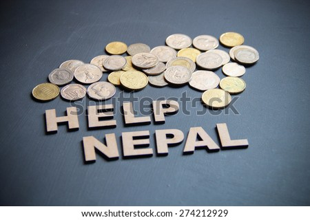 Help nepal with money is the concept here on blackboard. Wooden letters are here with different countries currencies.