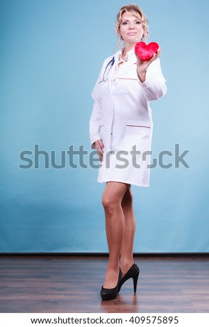 Help people concept. Medical idea of helping. Mature blonde happy doctor cardiologist with red heart enjoy her work. Middle aged woman wearing medic apron. - stock photo