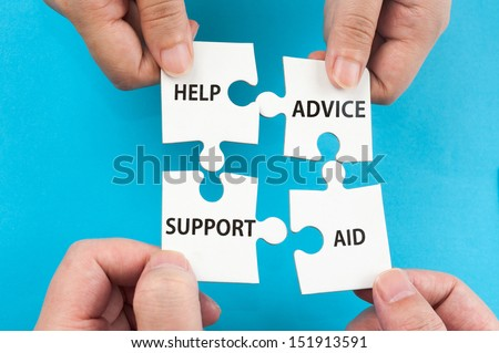 Help, support, aid and advice concept with two hands holding jigsaw puzzle pieces and putting them together - stock photo