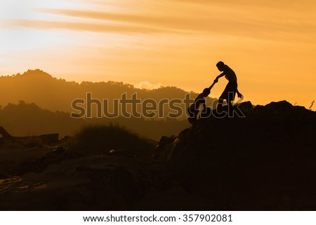 Help, support, Silhouette, mountain at sunset, one of them giving hand and helping to climb. - stock photo