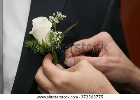 help the groom to pin a wedding flower to suit