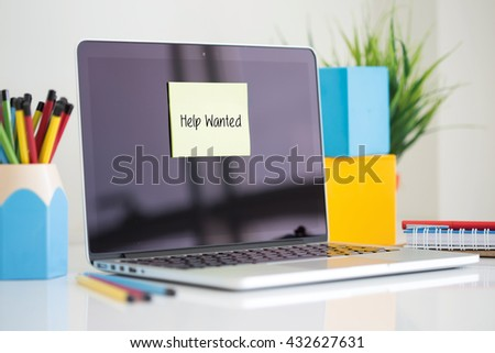 Help Wanted sticky note pasted on the laptop - stock photo