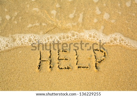 HELP - written in sand on beach texture - soft wave of the sea. - stock photo