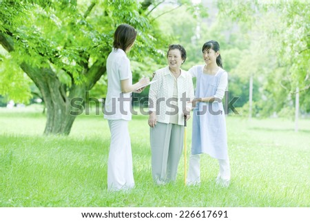 Helper and nurse and senior woman standing on the lawn - stock photo