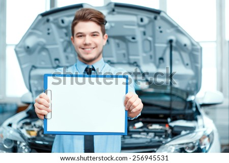 Helpful and client oriented. Selective focus image of a handsome smiling car assistance manager in formalwear standing on the background of the car and stretching out a clipboard with copy space - stock photo