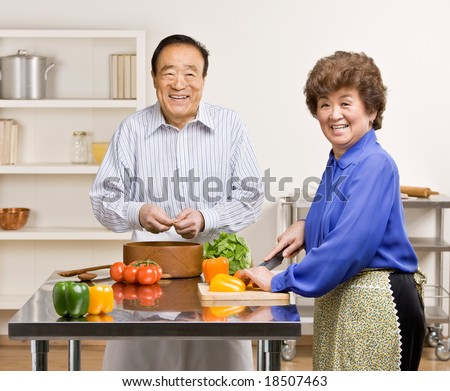 Helpful man preparing wholesome salad with wife in kitchen for dinner - stock photo