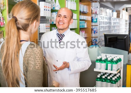 Helpful mature pharmacist consulting young woman in pharmacy and smiling - stock photo
