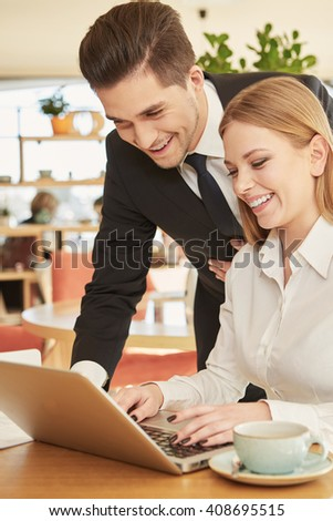 Helpful partner. Handsome cheerful businessman helping his smiling female colleague with documents on the laptop over lunch at the restaurant - stock photo