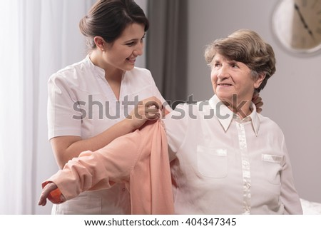 Helpful young caregiver giving the sweater to older woman - stock photo