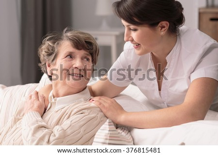 Helpful young pretty woman and lovely older lady - stock photo