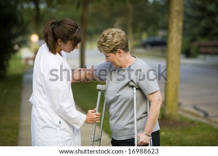 helping a patient with crutches - stock photo
