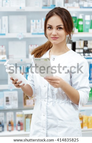 Helping every customer. Vertical shot of a pharmacist looking to the camera holding medications and a prescription posing in a pharmacy.  - stock photo