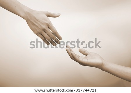 helping hand and hands praying.helping hand concept.hand of god giving the power to human's hand.abstract helping hand in sepia vintage tone colors concept. - stock photo