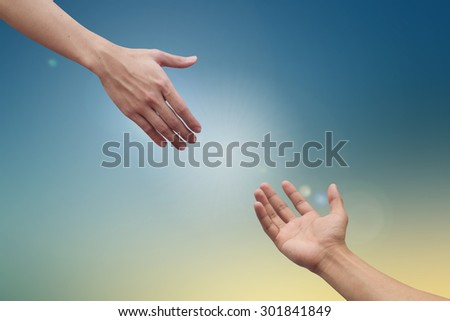 helping hand and hands praying on blurred colorful background , helping hand concept. - stock photo