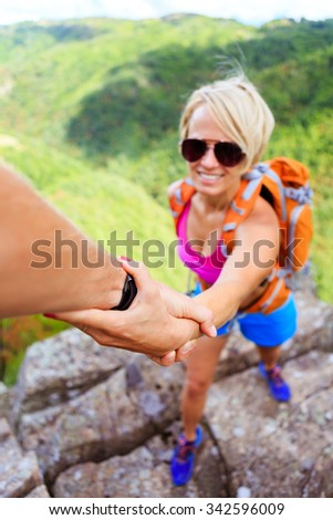 Helping hand couple, hiking help each other. Man and woman teamwork climbing or hiking with motivation and inspiration, beautiful inspirational landscape. Team sports and fitness. Focus on hands. - stock photo