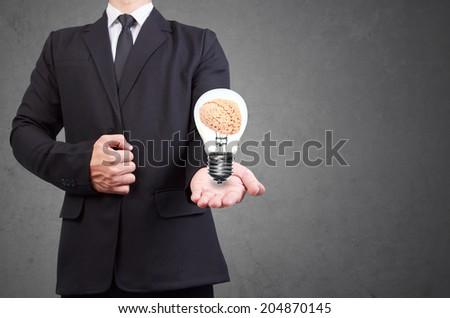 helping hand holding brain inside a light bulb idea concept for creativity - stock photo