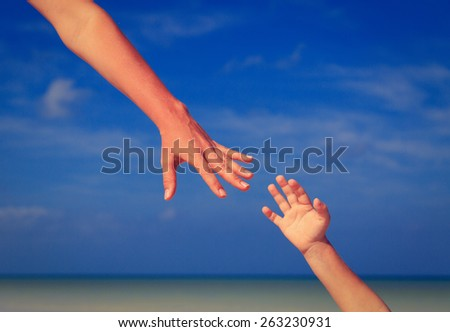 helping hand of mother and child on sky at the beach, care and protection - stock photo