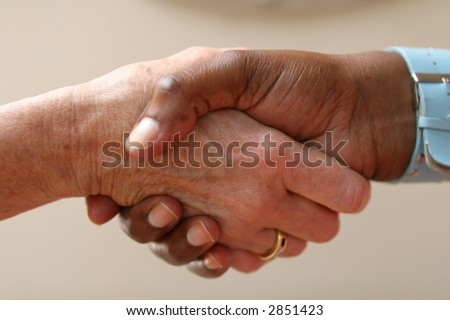 Helping hand shakes another hand as part of an agreement - stock photo