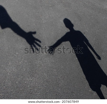 Helping Hand with a shadow of an adult hand offering help or therapy to a child in need as an education concept of charity towards needy kids and teacher guidance to students who need tutoring. - stock photo