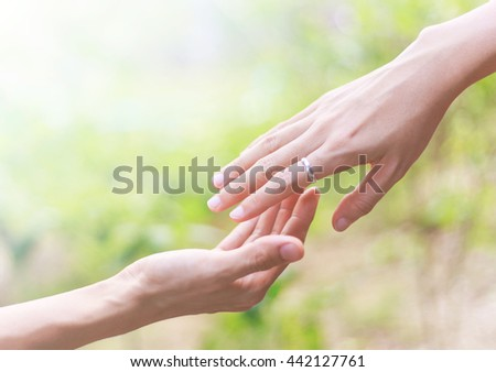 Helping hands - hands praying against nature blur background