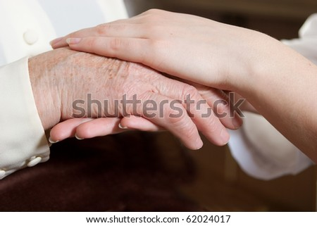 Helping hands: the nurse holds hands of the elderly female