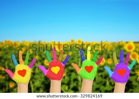 Helping hands with hearts on the palms against nature background. The eco friendly concept.