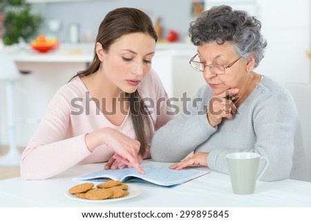 Helping her grandma do a crossword - stock photo