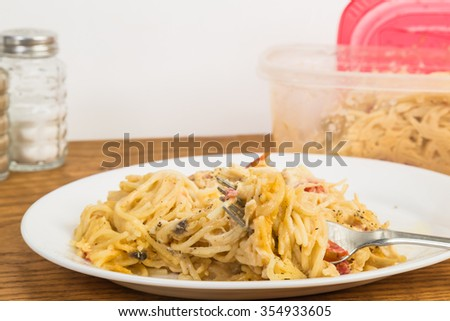Helping of leftover chicken spaghetti from plastic bowl heated in microwave and served on white plate. - stock photo