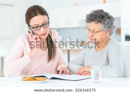 Helping senior lady with her finances - stock photo