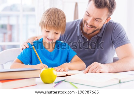 Helping son with schoolwork. Cheerful young father helping his son with homework and smiling while sitting at the table together  - stock photo