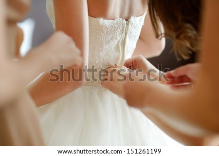 Helping the bride to put her wedding dress on - stock photo