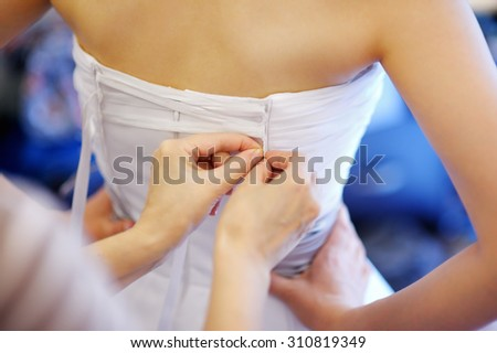 Helping the bride to put her wedding dress on, close up photo - stock photo