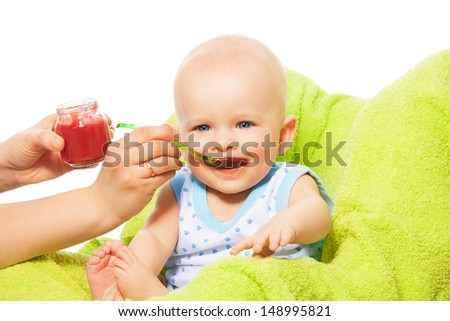Helping to eat cute happy little baby boy from the spoon - stock photo