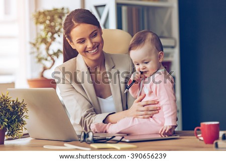 Helping to mommy. Little baby girl chewing pen while sitting on office desk with her mother in office - stock photo