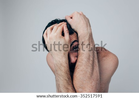 Helpless Naked man covered his face with his hands. Isolated on a light background - stock photo