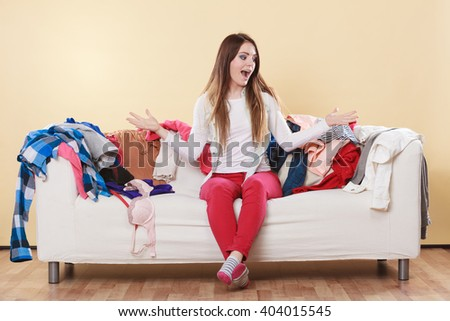 Helpless woman sitting on sofa couch in messy living room shrugging. Young girl surrounded by many stack of clothes. Disorder and mess at home. - stock photo