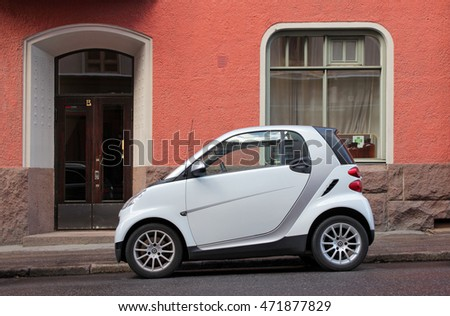 HELSINKI, FINLAND - AUGUST 10, 2016: Side view of small city car parked at the famous Ullanlinna District on Neitsytpolku street in Helsinki, Finland just after a rain shower, August 10, 2016.