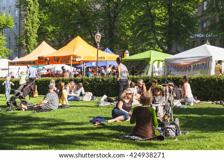 Helsinki, Finland - May 21, 2016: Helsinki Restaurant Day 2016. It is a traditional street carnival of food. Participants sign up on the website and get cooking. Citizens are relaxing on grass - stock photo