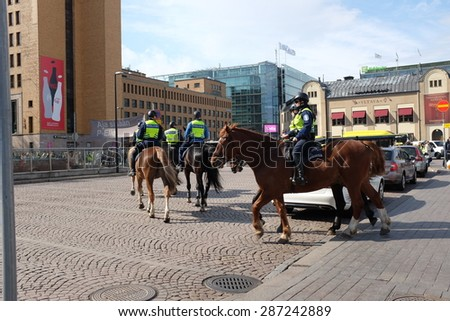 HELSINKI, FINLAND - MAY 21, 2015: Mounted police patrol in the center of the capital of Finland. - stock photo