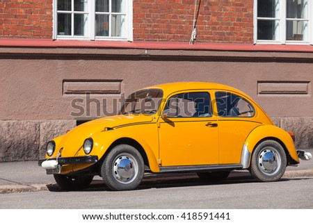 Helsinki, Finland - May 7, 2016: Old yellow Volkswagen beetle is parked on a roadside - stock photo