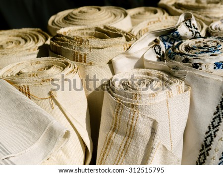 Hemp and linen fabric closeup. Trendy organic textile in retro style - natural  fabric of flax and cotton in rolls. Linen towels - homespun fabric of handwork on fair. - stock photo