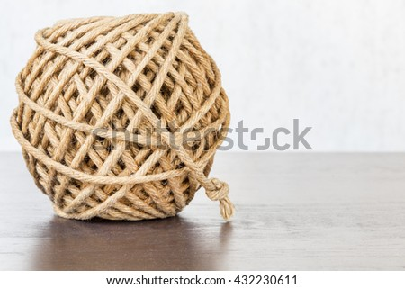 Hemp ball on wooden table with copyspace with selective focus - stock photo