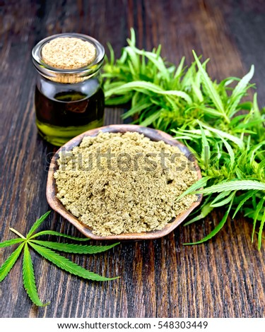 Hemp flour in a clay bowl in a glass jar oil, cannabis leaf on a background of wooden boards