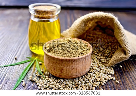 Hemp Flour in a wooden bowl, hemp seed in a bag and on the table, hemp oil in a glass jar, hemp leaf on the background of wooden boards - stock photo