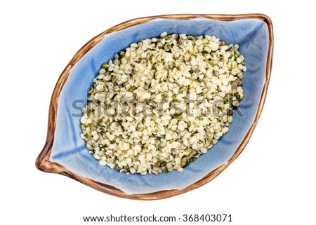 hemp seed hearts on an isolated leaf shaped ceramic bowl, top view - stock photo