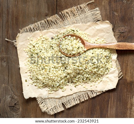 Hemp seeds with a spoon on a wooden table - stock photo